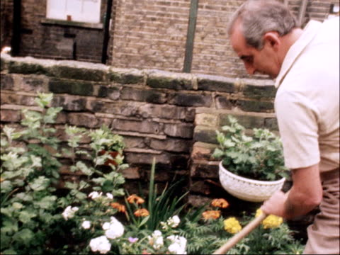 first anniversary of operation ENGLAND London Battersea EXT Keith Castle tending flowers in garden Keith Castle seated at easel painting picture New...