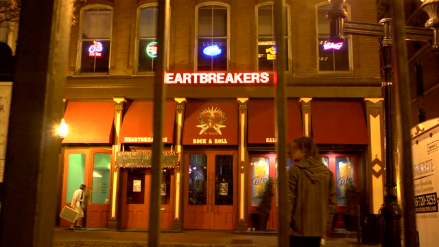 vidéos et rushes de heartbreakers rock & roll bar/nightclub entrance & facade across street as unidentifiable men enter & exit building w/ fence bars in fg - entrée