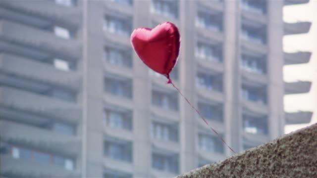 heart-shaped helium balloon tied to balcony of office building blowing in wind / london, england - hope concept stock videos and b-roll footage