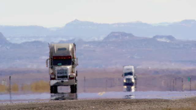 heat haze distort video of semi-trucks driving down a utah interstate surrounded by mountains on a sunny day - general view stock videos & royalty-free footage
