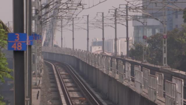 A heat haze distorts a view of birds flitting accross monorail tracks Mumbai Maharashtra India FKAD675A Clip taken from programme rushes ABQA810K