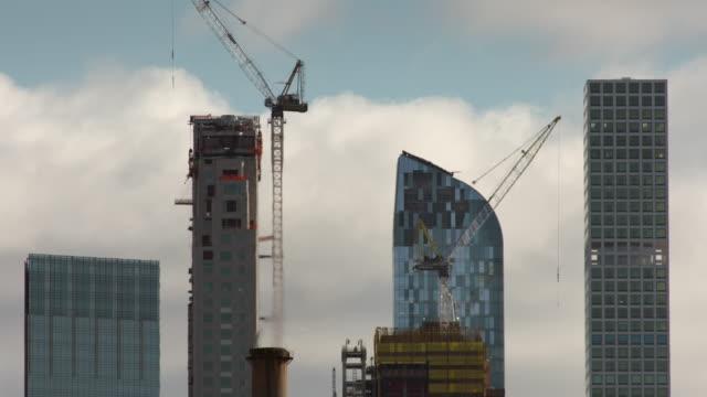 vídeos de stock, filmes e b-roll de heat haze distorts image of 4 new york city high rises against a cloudy sky. - onda de calor fenômeno natural