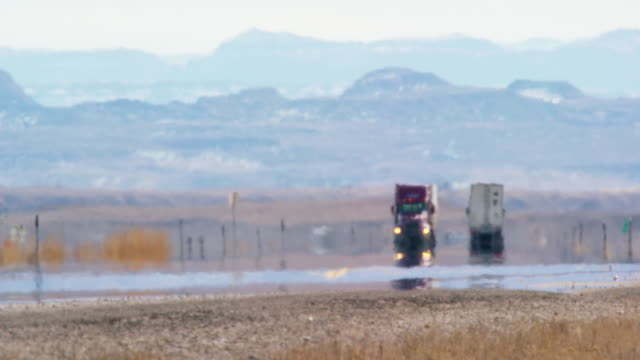heat haze distorts video of semi-trucks driving down a utah interstate surrounded by mountains on a sunny day - tarmac stock videos & royalty-free footage