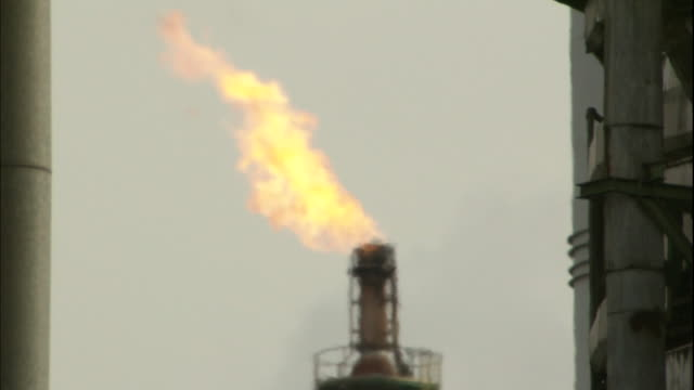Heat haze flickers in front of gas burnoff at oil refinery