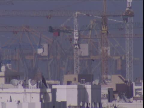 heat haze shimmers past mass of construction cranes above rooftops dubai - erezione video stock e b–roll
