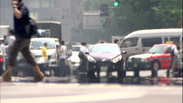 heat waves dance across a busy intersection in tokyo, japan. - 横断歩道点の映像素材/bロール