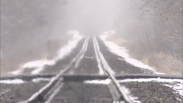 Heat waves rise over a snowy railroad track.