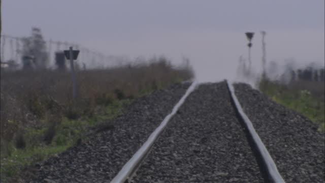heat waves shimmer over train tracks. - 熱波点の映像素材/bロール