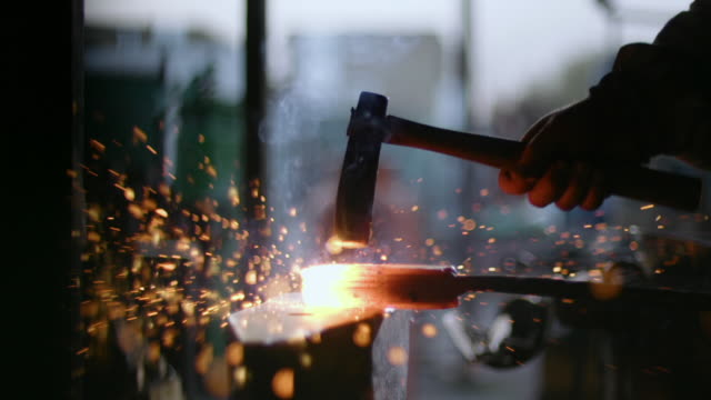 A heated block of steel is hammered on a workbench, producing red sparks.