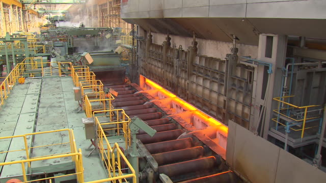 Heated iron ingot coming out of the machine in steel mill