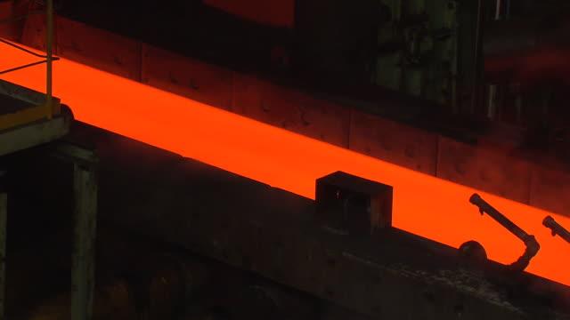 heated iron ingot moving through conveyor belt in steel mill - 鉄点の映像素材/bロール