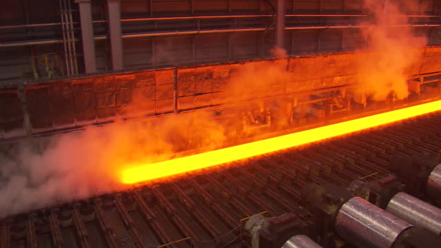 heated iron ingot moving through conveyor belt in steel mill - metallindustrie stock-videos und b-roll-filmmaterial