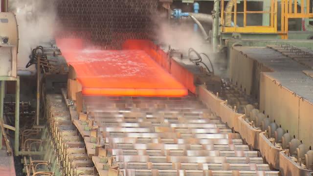 Heated iron ingot moving through conveyor belt