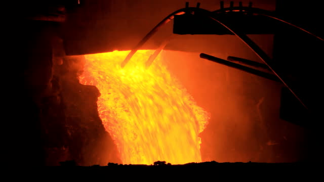 heated metal flowing from a furnace - blast furnace stock videos & royalty-free footage