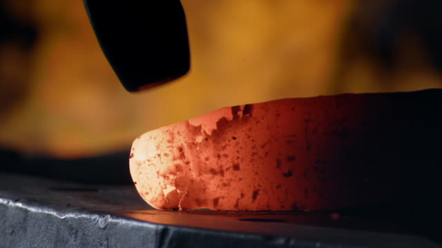 stockvideo's en b-roll-footage met heated steel is hammered into a blade shape with a hammer in a blacksmithing workshop. - staal