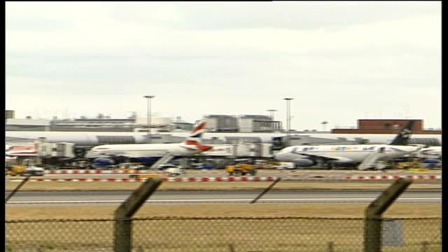 BA jet landing / planes on tarmac ENGLAND London Heathrow Airport British Airways passenger jet plane flying towards as lands PAN plane away on...