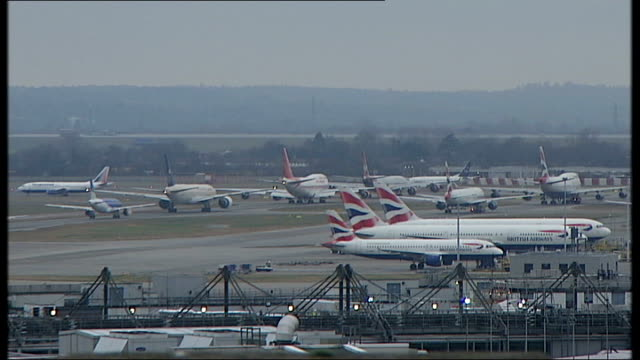passengers in crowded airport terminal planes on tarmac - ヒースロー空港点の映像素材/bロール