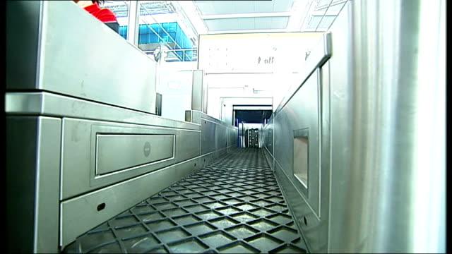 queues Bags being processed at unidentified checkin desk/ general views of escalators between floors in Terminal 5