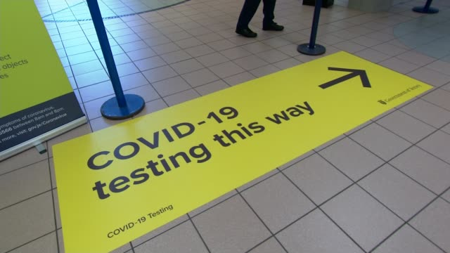 heathrow airport wants 'double testing' regime to reduce quarantine; jersey: jersey airport: int gv people in masks in queues at airport gv sign on... - quarantine stock videos & royalty-free footage