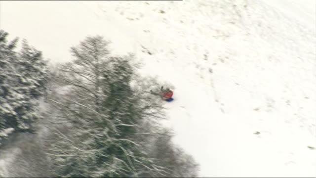 heathrow bosses warn of flight cancellations in bad weather lib / surrey box hill people sledging down hill - サリー州 ボックスヒル点の映像素材/bロール