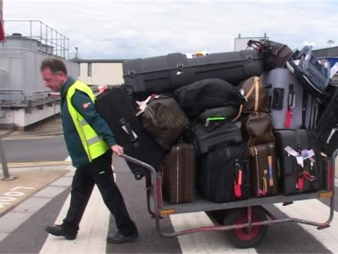 a heathrow porter strains to pull trolley laden with luggage for michael douglas catherine zeta jones and family staff member helps with movement - push cart stock videos & royalty-free footage