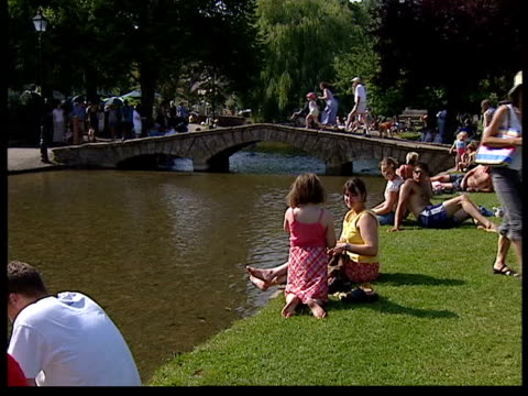 vídeos y material grabado en eventos de stock de record temperatures itn cotswolds people sitting on edge of river two boys playing in river young girls sitting on edge of river simon brown astonned... - cotswolds