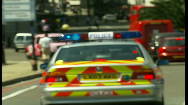 heatwave continues int paramedics driving across lambeth bridge behind police car and past prime minister's police escort - lambeth stock videos & royalty-free footage