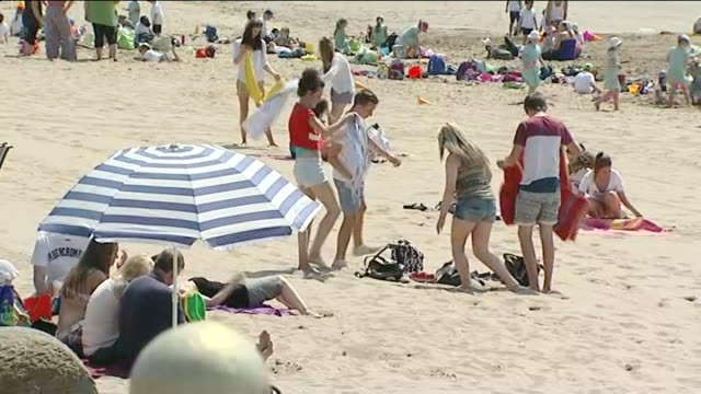 Met Office issue health warning ENGLAND People wading in sea wearing swimming costumes People sitting and sunbathing on beach Women in shorts and...