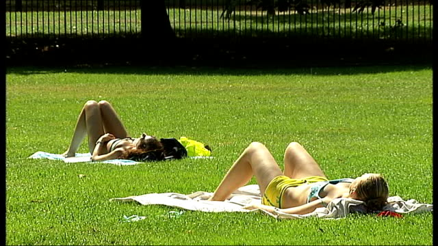 met office issue health warning england london ext women in bikini swimming costumes sunbathing in park woman in park eating ice cream people along... - swimming costume stock videos and b-roll footage
