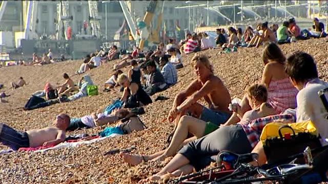 vídeos y material grabado en eventos de stock de heatwave forecast across britain england east sussex brighton ext people sitting and lying on brighton beach sunbathers lying on pebble beach man and... - east sussex