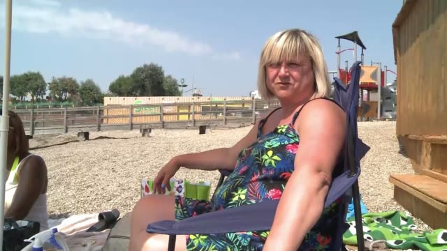 vídeos de stock, filmes e b-roll de hot weather in britain impacting summer holiday plans uk essex southend people sat on the beach and swimming in the sea along promenade beachgoers... - onda de calor fenômeno natural