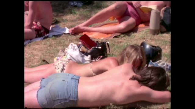 vídeos de stock, filmes e b-roll de hottest june day for 41 years 1976 people sunbathing on grass - 1976