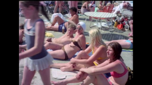 vídeos de stock, filmes e b-roll de hottest june day for 41 years 1976 people sunbathing woman using standpipe on street and women along with containers of water - 1976
