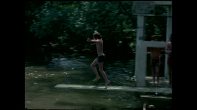 Hottest June day for 41 years 1976 Women sunbathing in bikinis on grass Boy diving into water at Hampstead Heath Men sunning themselves and people in...