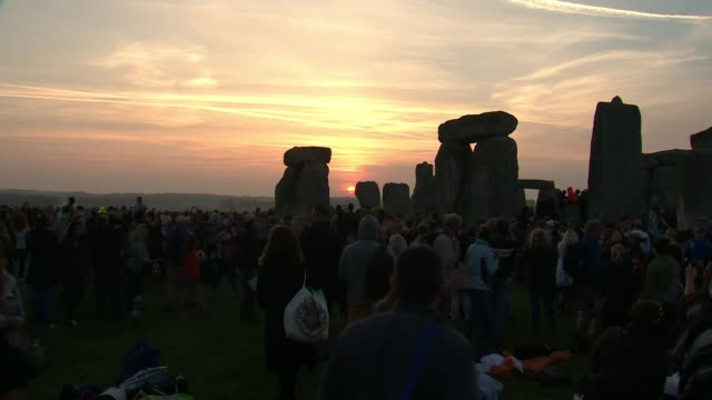 Hottest June day for 41 years ENGLAND Wiltshire Stonehenge Various of sun rising on distant skyline with crowds gathered in foreground at Stonehenge...