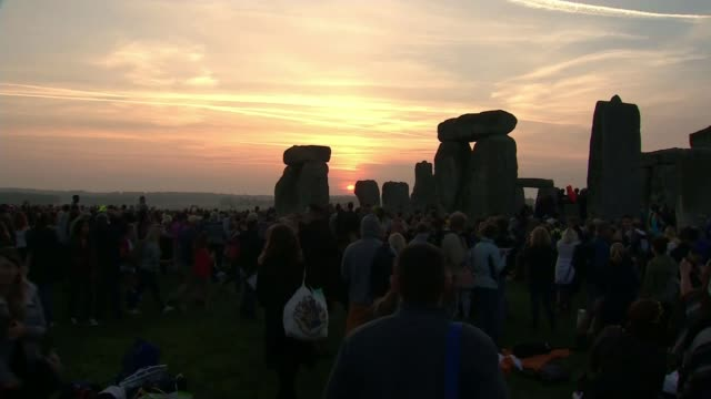 vídeos y material grabado en eventos de stock de hottest june day for 41 years; england: wiltshire: stonehenge: ext / dawn sun rising on distant skyline with crowds gathered in foreground at... - solsticio de verano