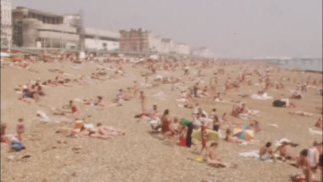 vídeos de stock, filmes e b-roll de hottest june day for 41 years tx east sussex brighton various of sunabthers on beach at brighton/ london popel swimming in serpentine in hyde park... - 1976