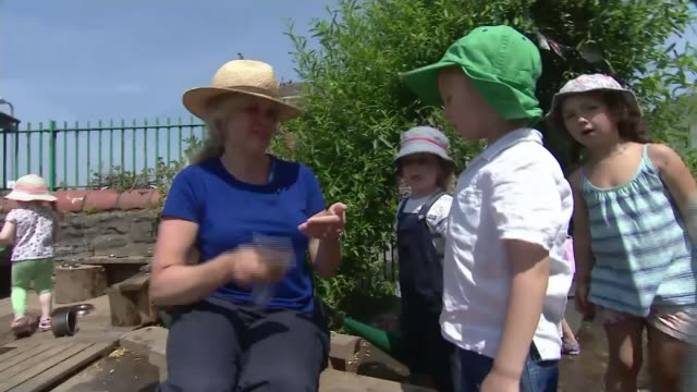 Hottest June day for 41 years WALES Cardiff Teacher putting sun protection cream onto children's faces in primary school playground/