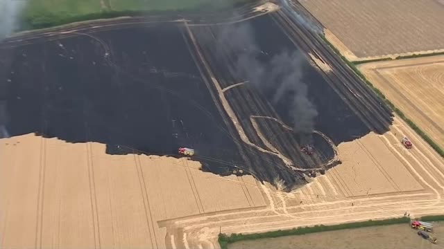impact on ice cream production england nottinghamshire tithby smoke and flames rising from burning crop field air view firefighters at scene of crop... - northern europe stock videos & royalty-free footage