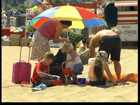 heatwave itn children playing on beach lms donkeys along beach carrying children on backs man lying sleeping on beach family under parasol people... - parasol stock videos & royalty-free footage