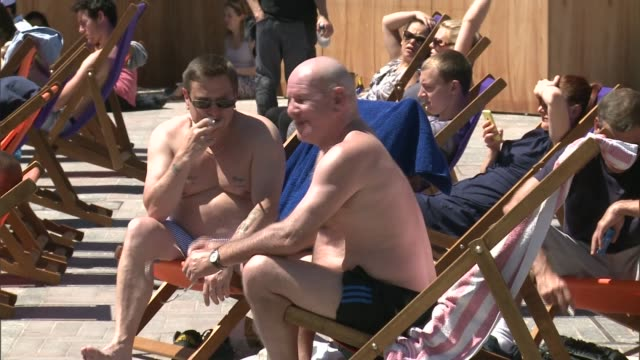 heatwave alert may be triggered; feet of person jumping in shallow water people sunbathing in deckchairs kevin elliston interview sot close shot... - deck chair stock videos & royalty-free footage