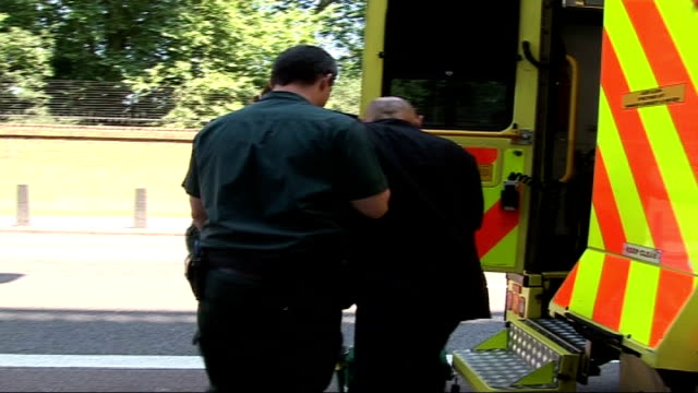 record temperatures in britain; london: ext back view of ambulance staff leading man with heatstroke to ambulance - itvイブニングニュース点の映像素材/bロール