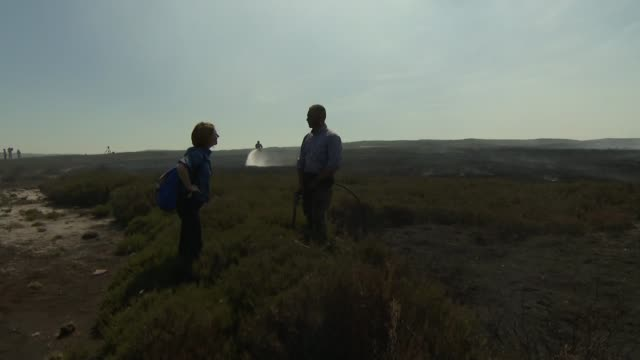 saddleworth moor fire fires 'could take weeks' to die out say fire brigade uk greater manchester saddleworth moor flame and smoke man spraying ground... - fire hose stock-videos und b-roll-filmmaterial