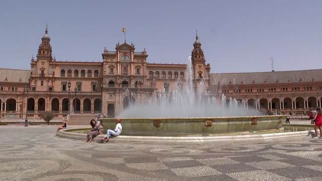 spain prepares for recordhigh temperatures spain andalusia seville ext woman along holding scarf over head boy reaching into fountain general view... - städtischer platz stock-videos und b-roll-filmmaterial