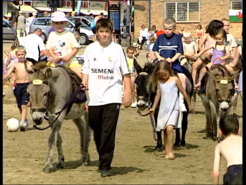 heatwave travel chaos/holidaymakers itn scaroborough people enjoying sunshine on scarborough beach boy building sandcastle children along on donkeys... - 英国スカーブラ点の映像素材/bロール