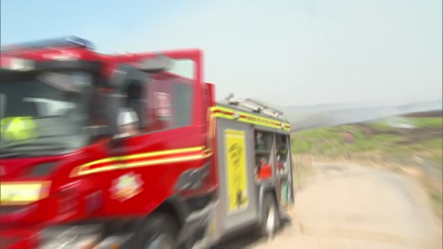 wildfires on winter hill england greater manchester near bolton winter hill ext smoke rising from fire / firefighters beating fire / firefighter... - bolton greater manchester stock videos and b-roll footage