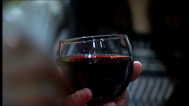 Heavier drinkers to be offered a tablet to curb consumption R19021401 / 1922014 London London South Bank University Glass of red wine being held...