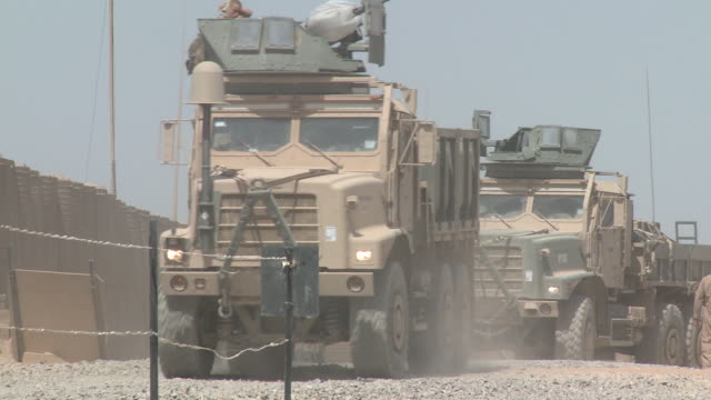 Heavily armed US. Marine heavy duty trucks depart from a logistics base.