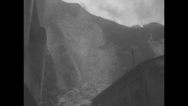 heavily damaged building with pan up to towering cliff and collapsed debris / man poking edge of cliff with cane and pan down hundreds of feet to... - kreidefelsen stock-videos und b-roll-filmmaterial