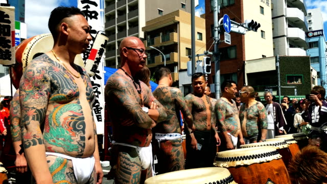 heavily tattooed japanese men wait near asakusa temple as they participate on the third and final day of sanja festival on may 20 2018 in tokyo japan... - shitamachi stock videos and b-roll footage